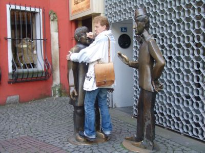 The walking tour guide with the Tünnes und Schäl statues, to the south-west of Gross St Martin
