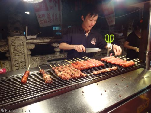 Cooking meat on a stick at Shilin Night Markets