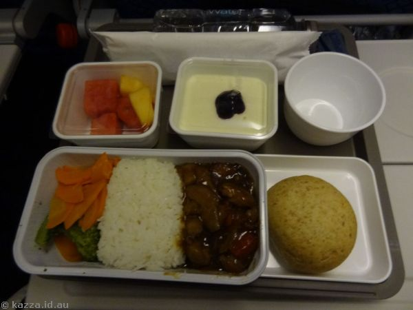 Dinner on the plane - Three cup chicken, broccoli, carrot and steamed jasmine rice, with seasonal fresh fruits, bread and butter, cheese mousse cacke with blueberry compote
